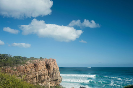 Waves-breaking-against-granite-cliff-at-Wilyabrup-main-bluff-under-blue-sky-with-fluffy-white-cloud,-Margaret-River-area,-Western-Australia---shutterstock_291714812